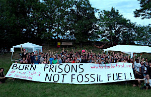 "people in a field with banner: ""Burn Prisons not fossil fuels"""
