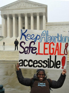 """smiling woman wearing t-shirt that says """"I had an abortion"""", holding a sign that reads """"Keep abortion safe, legal, & accessible."""""""