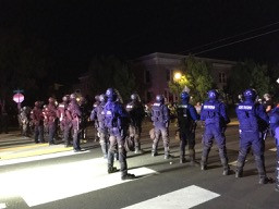 Approximately fifteen Oregon State Troopers stand in a riot line on Denver St in Kenton, Portland
