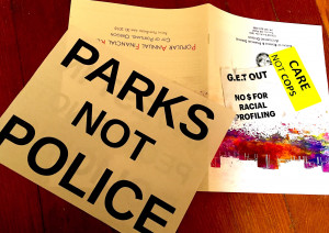 "handouts from forum: sign ""Parks not Police""; sticker ""care not cops"""