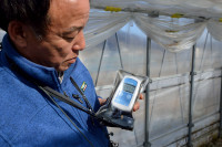 Takeshi Yamakawa of Tokyo Shimbun shows that the air dose level inside a greenhouse in Iitate Village is 0.433 μSv/hour, nearly twice as high as the government standard for outdoors of 0.23 μSv/hour.  (Photo courtesy of U. G. Kaneko)